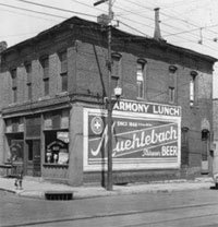 Harmony Lunch restaurant at 4th and Grand, showing Muehlebach Beer sign on the side.