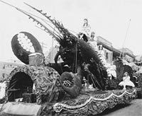 Women in costume atop float bearing oversized lobster