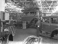 Interior view of unidentified car assembly plant, showing assembly line works, chassis, and workers