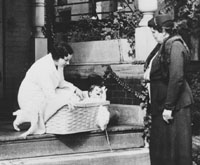 Nurse with baby in basket on porch of K. C. Cradle. K.C., Mo.
