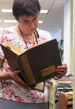 Reference librarian Judy Klamm examines a nearly 80-year-old reference book while weeding at the Central Library.